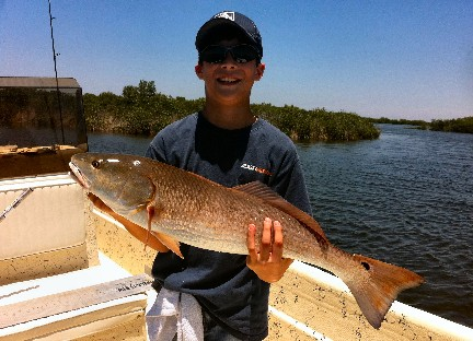 Mykel Murphy, son of HCFC member Mike Murphy, proudly displays the 29.5 inch Redfish he landed during the 2012 Spring Tournament.